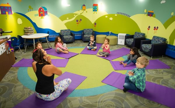 A teacher and children sitting in a circle on yoga mats doing yoga